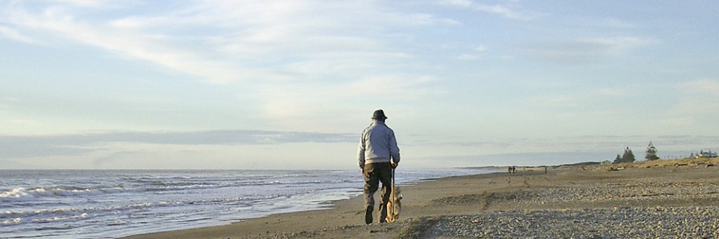 Man walking dog on Otaki Beach