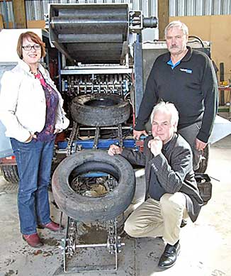 Ōtaki Ward Councillor Penny Gaylor is shown the portable tyre shredder by Entyre's Reiner Wenzel (crouching) and Nigel Pritchard of Riverbank Engineering.