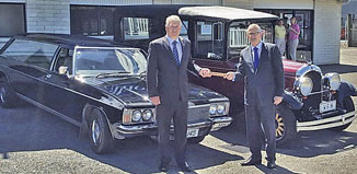 Michael Hill of Harvey Bowler with his classic Statesman receives the baton from Graeme Rolston of Waikanae Funeral Home with his vintage hearse.