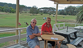 Tom Southgate & Bella Ansell, sitting at 'Annie's Table' with the busy green golf course behind