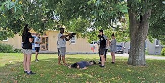 One student plays dead while the rest learn film-making