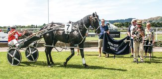 Jet Black Power and driver/trainer, Nicky Chilcott arrive back in the birdcage after winning the Otaki Cup on day two, completing a double winning the Wellington Trotting Cup on Friday, day one of the two day meet. Kapiti Coast Harness Racing's patron, Trevor Wylie is at microphone with president, Mary Colman right, before presenting the cup to his owners