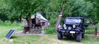 Behind the tent is an A-frame caravan. Behind the 4wheel drive is a gazebo.